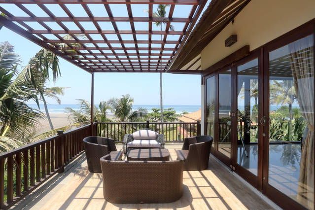 Upstairs terrace directly overlooks surf break and river.
