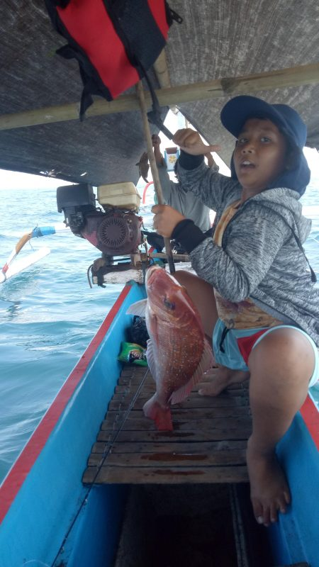 Person catching a fish from Balian fishing boat